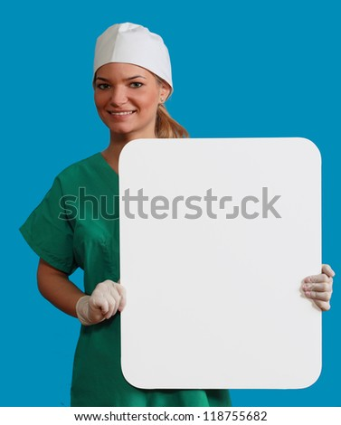 A smiling young woman doctor holding an empty white bill board against a blue background.