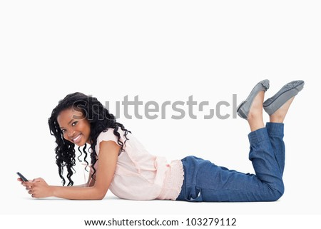 A smiling young woman is looking at the camera and lying on the floor holding a mobile phone - stock photo