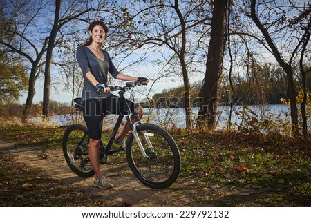 a smiling young woman on a mountain bike - stock photo