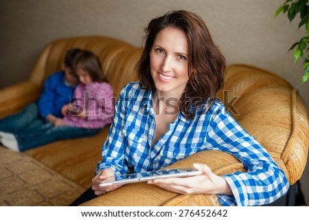 A smiling young woman sits on a sofa with a digital tablet, her children on a background. - stock photo
