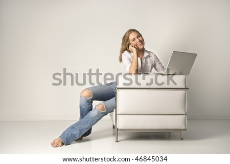 A smiling young woman sitting in a white armchair with a laptop computer, talking on a cell phone. Horizontal shot.