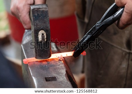 A smith forging a horse shoe on an anvil