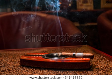 a smoking expensive cigars in the ashtray on the table - stock photo