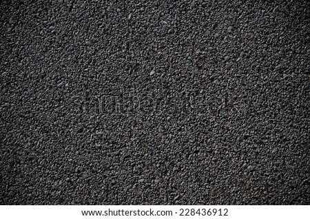 A smooth dark grey asphalt pavement texture with small rocks - stock photo