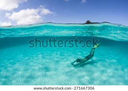 A snorkeler swims in a beautiful lagoon in Raja Ampat, Indonesia. This region is in the heart of the Coral Triangle, harbors high marine biodiversity and offers world class diving and snorkeling. - stock photo