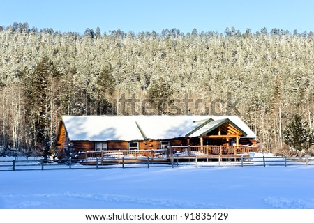 A snow capped mountain cabin resort surrounded by snow-covered trees - stock photo