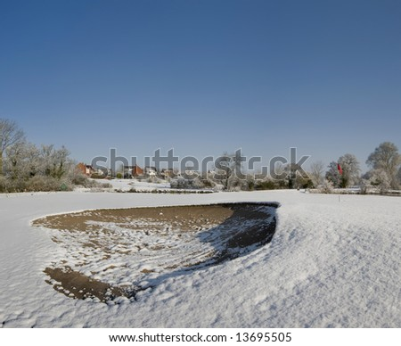 A snow covered hole on a golf course - stock photo