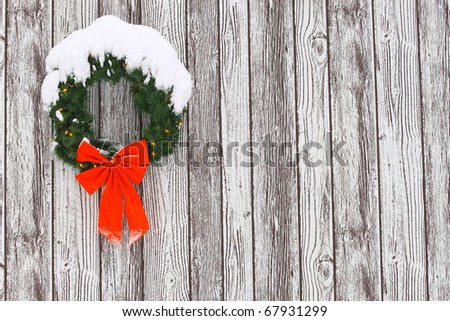 a snow covered lighted christmas wreath with a big red bow with icicles on it against a wooden pattern while it is snowing out for your use with room for your text. - stock photo