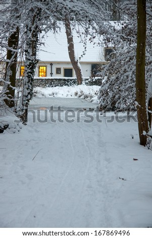 A snow-covered path through the forest which ends at lighted house in The Netherlands.