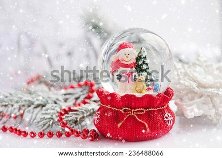 A snow globe with snowman on background spruce branches with snow - stock photo