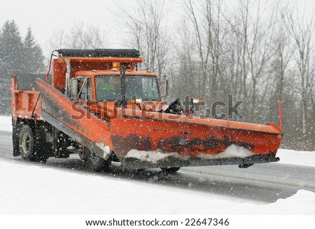 A snow plow truck ready for the storm - stock photo