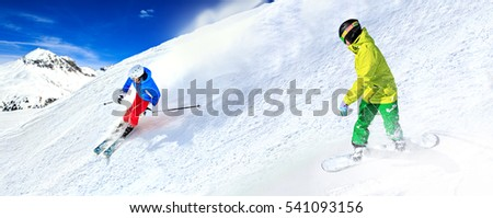 A snowboarder and ski driver on the piste in Alps in Austria