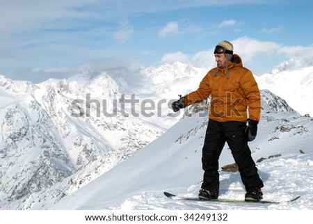 a snowboarder costs at top of mountain and shows a hand on the blue sky