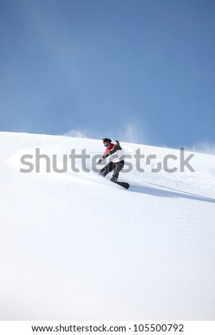 A snowboarder gliding down a slope - stock photo