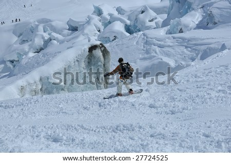 a snowboarder moving down and ice fall and being watched by people at the bottom. Large blocks of ice seperated by deep crevasses make this quite a dangerous place to ski