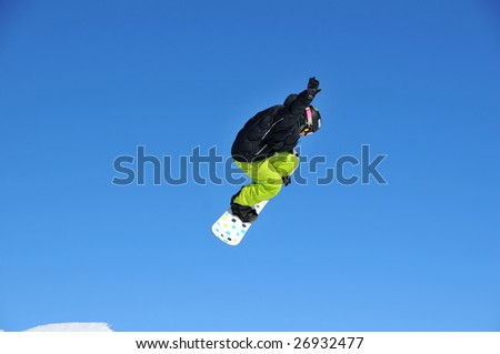 a snowboarder  performing a high jump into a blue sky