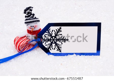 A snowman on a candy cane with a gift tag blue background, Christmas Time - stock photo