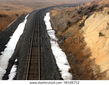 A Snowy Railroad Track Disappearing Around a Distant Curve