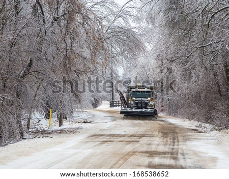 A snowy road being plowed in winter. - stock photo