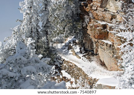 A snowy trail leads around the side of the Sandia Mountains just after the first snow of winter - horizontal orientation - stock photo