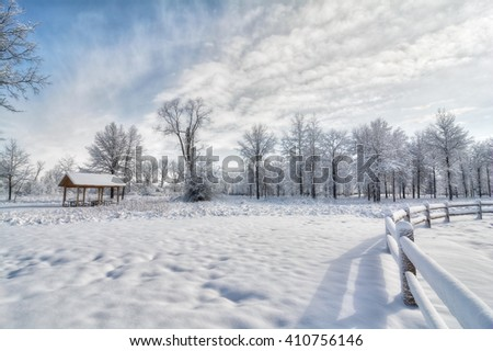 A snowy winter scene in a park with a split rail wood fence and the snow clinging to the trees.
