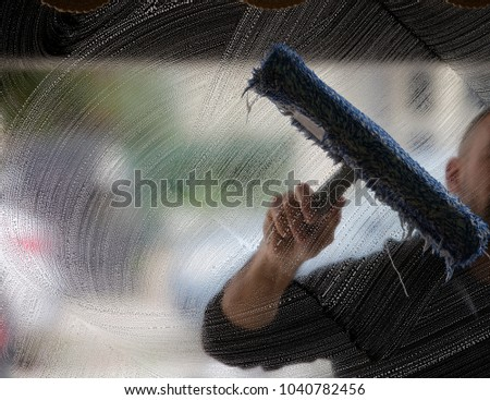 a soapy window with a squeegee cleaning the glass