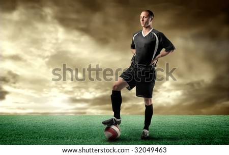 a soccer player standing in a grass field - stock photo