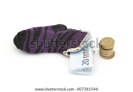 A sock filled with euro notes and next to a pile of coins - stock photo