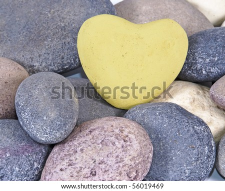 a Soft yellow coloured stone heart surounded by other natural stones - stock photo