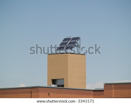 A solar panel sits on a tower on top of a school building.