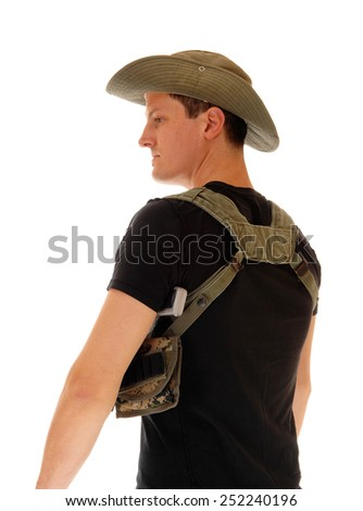 A soldier in a black t-shirt and pistol holster, wearing a hat, standing from the back, isolated for white background.  - stock photo