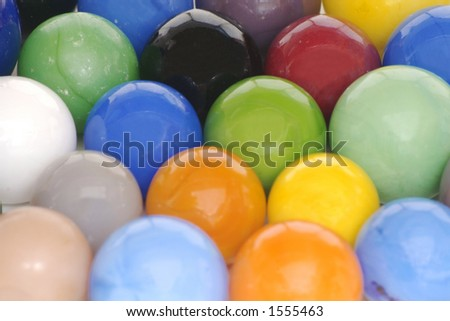 A solid background of brightly colored toy glass marbles. - stock photo