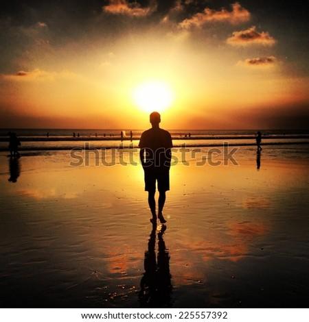 A solitary man walking along the beach toward the setting sun. - stock photo