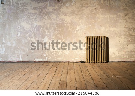 A solitary radiator standing in a bare room in need of decorating.