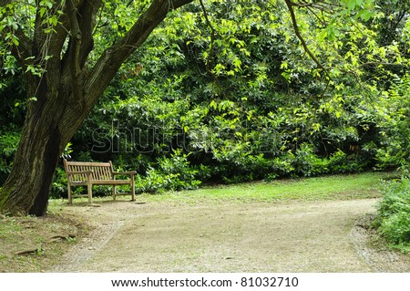 A solitary wooden bench surrounded by trees and a nice walkway in a quiet park - stock photo