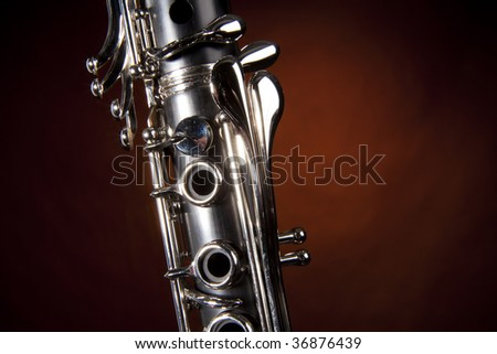 A soprano clarinet isolated against a gold spotlight background in the horizontal format.