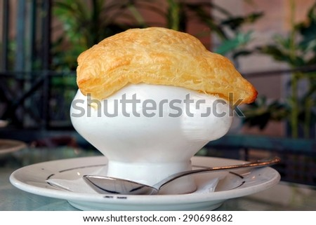 A soup dish with corn potage and crisp puff pastry. The image employs selective focus and shallow depth of field.  - stock photo