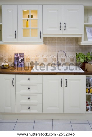 A spacious modern white kitchen - stock photo