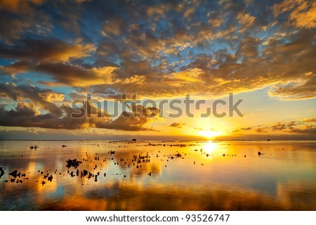 A spectacular golden sunset seen from Reunion Island reflected on the calm surface of the Indian Ocean. - stock photo