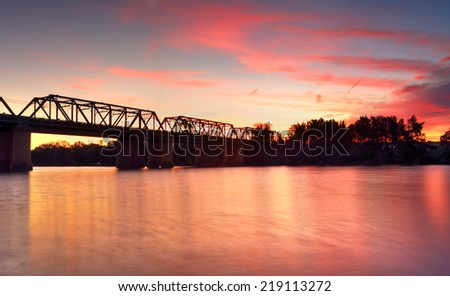 A spectacular spring sunset erupted into fiery spectrum of reds over the old grand Victoria Bridge which crosses the Nepean River at  Penrith.   - stock photo