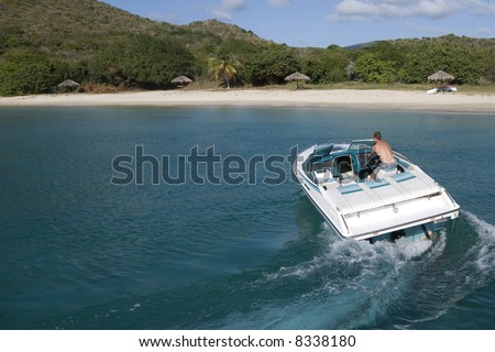 A speedboat in the turquoise waters of the Caribbean. - stock photo