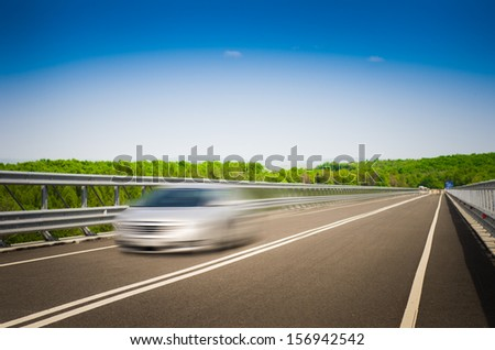A speeding car on a straight road on a sunny summer day with a blue sky background - stock photo