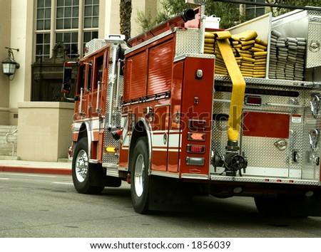 A speeding fire truck turns. - stock photo