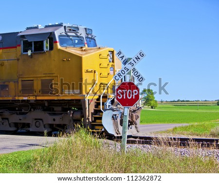 A speeding train crossing a road in rural America - stock photo