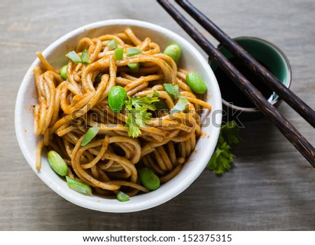 A spicy Asian noodle dish with chopsticks.