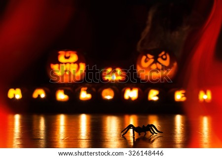 A spider is running in front of illuminated Halloween pumpkins - stock photo