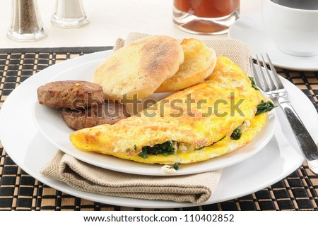 A spinach and feta cheese omelet with sausage and an english muffin - stock photo