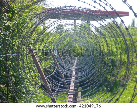 a spiral of sharp rusty barbed wire - stock photo