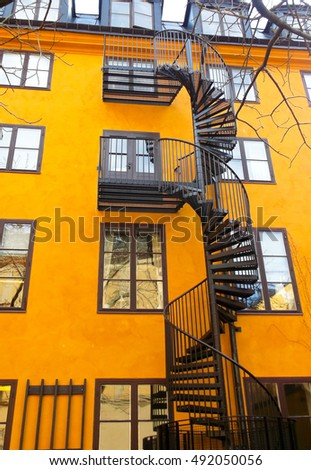 a spiral wrought-iron staircase on the background of yellow building staircase