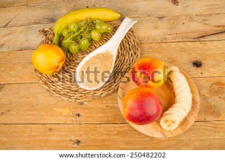A spoon full of brewers yeast surrounded by fresh fruit - stock photo